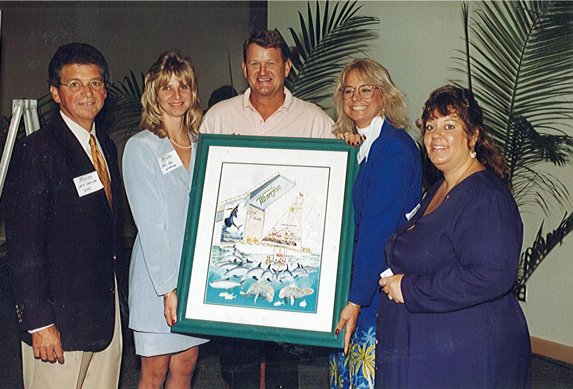 Artist Guy Harvey with Winterfest CEO Lisa Scott Founds revealing the 1998 parade poster